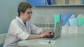 Koncentrerad kvinnlig doktor i exponeringsglas som skriver på bärbara datorn i hennes kontor arkivfilmer
