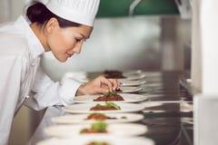 Koncentrerad kvinnlig kock som garnerar mat i kök arkivbilder
