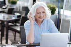 Koncentrerad kvinnlig seende skärm av hennes bärbar dator Royaltyfria Foton