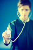 Koncentrerad läkare med stetoskopet Arkivfoton