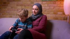 Koncentrerad liten pojke och hans muslim moder i hijab som tillsammans spelar videogamen med styrspaken hemma lager videofilmer