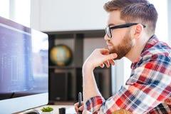 Koncentrerad man i exponeringsglas som drar ritningar på datoren royaltyfri bild