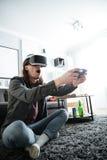 Koncentrerad man som hemma sitter inomhus leklekar Fotografering för Bildbyråer