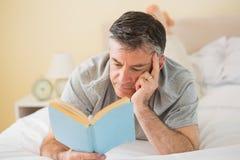 Koncentrerad man som läser en bok på hans säng Royaltyfri Bild