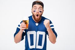 Koncentrerad manfan i blå t-skjorta som dricker öl Fotografering för Bildbyråer