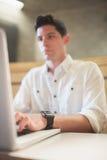 Koncentrerad manlig student som använder bärbara datorn arkivbilder