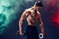 Koncentrerad muskulös man som gör övning med hanteln Arkivfoton