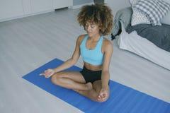 Koncentrerad praktiserande yoga för kvinna på mattt royaltyfria bilder