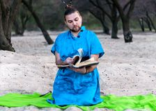 Koncentrerad stilig skäggig man i blått kimonosammanträde som bläddrar igenom den stora boken och läser på den sandiga stranden royaltyfria foton