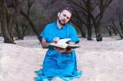 Koncentrerad stilig skäggig man i blått kimonosammanträde som bläddrar igenom den stora boken fotografering för bildbyråer