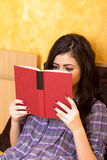 Koncentrerad tonårs- flicka som ligger i säng och läsning en bok Arkivfoton