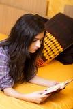 Koncentrerad tonårs- flicka som ligger i säng och läsning en bok Arkivbilder