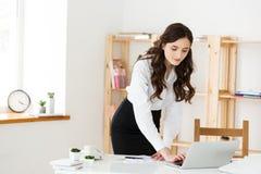 Koncentrerad ung härlig affärskvinna som arbetar på bärbara datorn och dokument i ljust modernt kontor royaltyfri bild