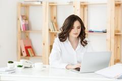 Koncentrerad ung härlig affärskvinna som arbetar på bärbara datorn och dokument i ljust modernt kontor royaltyfri foto