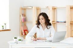 Koncentrerad ung härlig affärskvinna som arbetar på bärbara datorn och dokument i ljust modernt kontor arkivfoton