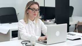 Koncentrerad ung kvinna i exponeringsglas som skriver på bärbara datorn på hennes kontorsskrivbord lager videofilmer