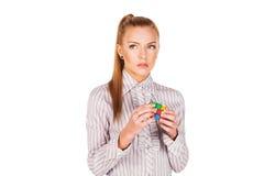 Koncentrerad ung kvinna lösa Rubik'sens kub royaltyfri bild
