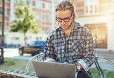 Koncentrerad ung man med hans bärbar dator arkivbild