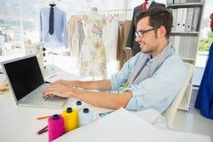 Koncentrerad ung manlig modeformgivare som använder bärbara datorn royaltyfri fotografi