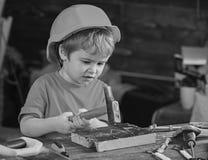 Koncentrerad unge som arbetar med hammaren Pys som vinner ny expertis Förskolebarnet som lär att bulta, spikar royaltyfri fotografi