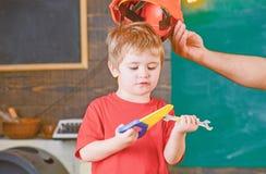 Koncentrerad unge som ner ser på hjälpmedel i hans händer Pojke som lär ny expertis Pappa som av tar hjälmen från son arkivbilder