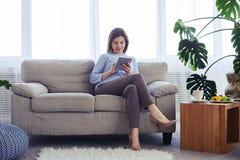 Koncentrerad vuxen kvinnlig som arbetar i bärbar dator, medan sitta på sof Royaltyfri Foto