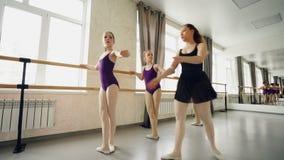 Koncentrerade flickor lär grundläggande balettpositioner i dansskola med den försiktiga läraren som hjälper dem för att styra arkivfilmer