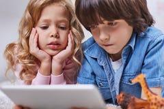 Koncentrerade involverade barn som surfar internet på den moderna grejen Arkivbild