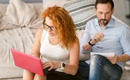 Koncentrerade par som hemma gör deras jobb arkivbild