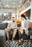 Koncentrerade par som kontrollerar färgrika prövkopior och diskuterar uppmärksamt royaltyfri foto
