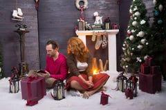 Koncentrerade par som ser mobiltelefonen mot julbakgrund arkivfoton