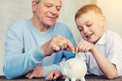 Koncentrerade släktingar som sätter ett mynt in i en moneybox fotografering för bildbyråer