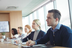 Koncentrerat affärsfolk som sitter på konferenstabellen under möte arkivbild