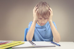 Koncentrerat barn som hemma gör hans läxa Pojkesammanträdet och se in till böcker och anteckningsböcker royaltyfria foton