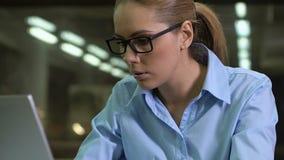 Koncentrerat företagsarbetarglasögon som skriver datoren, nattövertid, stopptid arkivfilmer