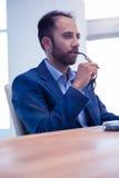 Koncentrerat hållande glasögon för affärsman på skrivbordet royaltyfri fotografi