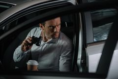koncentrerat hemligt manligt medel som gör bevakning vid kikare och dricker kaffe royaltyfri bild