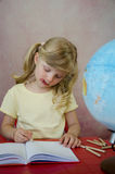 Koncentrerat liten flicka, notepad och jordklot royaltyfria bilder