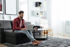 Koncentrerat sammanträde för ung man på soffan genom att använda bärbar datordatoren royaltyfria foton