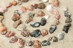 Koncentriska cirklar för kiselsten på selektiv fokus för sand Arkivfoto
