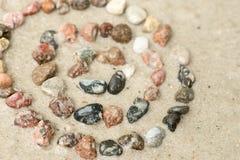 Koncentriska cirklar för kiselsten på selektiv fokus för sand Arkivbild