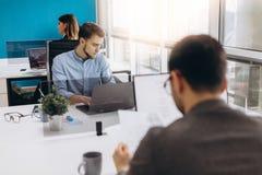Koncentrujący na pracie Skoncentrowany młody broda mężczyzna pracuje na laptopie podczas gdy siedzący przy jego pracującym miejsc obrazy stock