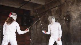 Koncentrujący i sprężający szermierze walczą z sabers w ciemnym pokoju zbiory wideo