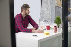 Koncentrujący na pracie Skoncentrowany młody broda mężczyzna pracuje na laptopie podczas gdy siedzący przy jego pracującym miejsc obraz stock