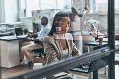 Koncentrujący przy pracą Nowożytna młoda kobieta używa komputer podczas gdy wo zdjęcie royalty free
