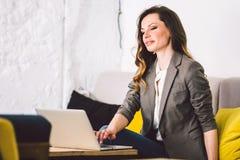 Koncentruj?cy przy prac? Ufna młoda dorosła w średnim wieku kobieta w mądrze przypadkowych ubraniach, pracujący na laptopie, sied zdjęcie stock