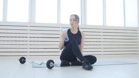 koncepcja kulowego fitness pilates złagodzenie fizycznej Młodej kobiety woda pitna po sport aktywność w białym wnętrzu zbiory