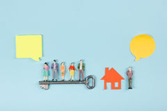 koncepcja real nieruchomości Mowa bąble i ludzie zabawek obliczają budowę, buduje Papierowy modela dom z kluczem na błękicie Obraz Royalty Free