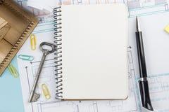 koncepcja real nieruchomości Pusty biały notatnik na architektonicznym biurko stołu projekta tle z kluczem, pióro, mały dom zdjęcia royalty free