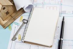 koncepcja real nieruchomości Pusty biały notatnik na architektonicznym biurko stołu projekta tle z kluczem, pióro, mały dom Obrazy Royalty Free